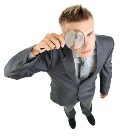 Young businessman looking through magnifying glass isolated on white photo