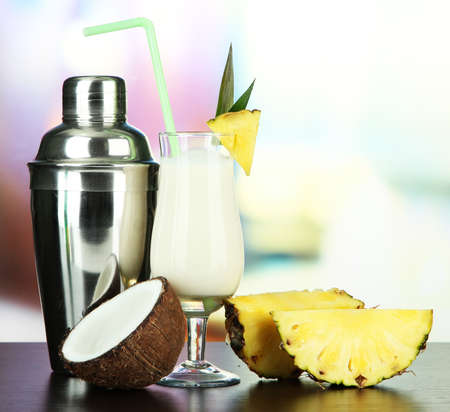 Pina colada drink in cocktail glass and metal shaker, on bright background photo