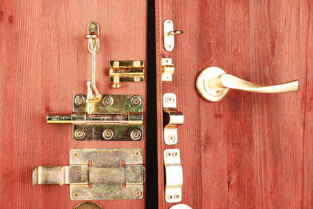 pawl: Metal bolts, latches and hooks in wooden open door close-up