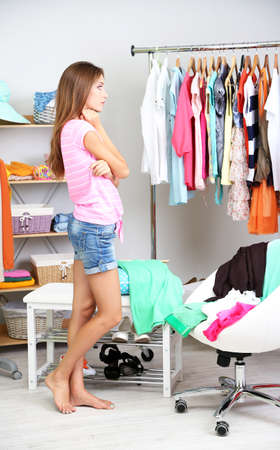 Beautiful girl thinking what to dress in walk-in closet photo