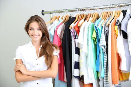gray clothing: Beautiful young stylist near rack with hangers