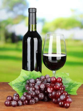 Uvas maduras, botella y vaso de vino en el fondo brillante