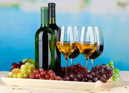 Wine bottles and glasses of wine on tray, on bright background Stock Photo - 21767866
