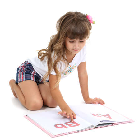 shyness: Little girl sitting on floor with book isolated on white Stock Photo