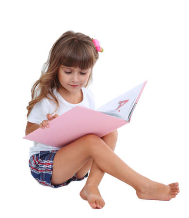 coquette: Little girl sitting on floor with book isolated on white Stock Photo