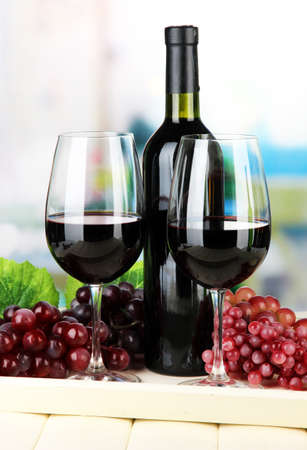 Ripe grapes, bottle and glasses of wine on tray, on bright background Stock Photo - 21828694