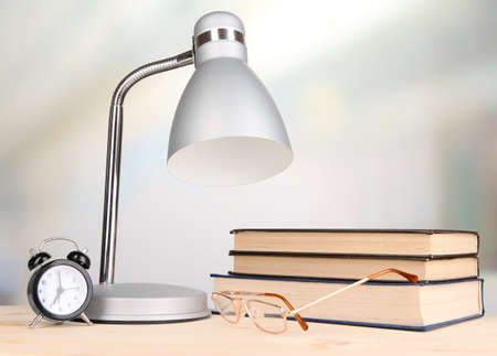 Table lamp and books on desk in room photo