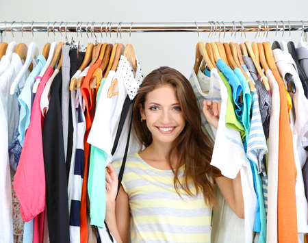 moda ropa: Mujer joven hermosa cerca estante con perchas