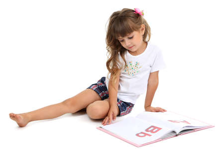 Little girl sitting on floor with book isolated on white Stock Photo