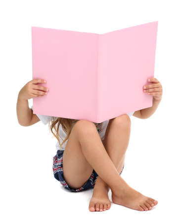 squat: Little girl sitting on floor with book isolated on white Stock Photo
