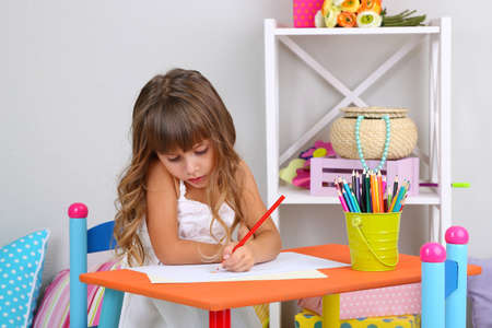 little table: Little girl draws sitting at table in room on grey wall