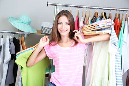 Beautiful girl with lots  clothes in room background photo