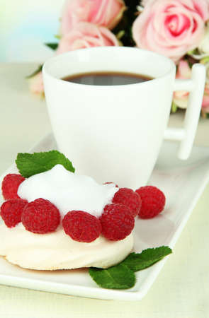 Tasty meringue cake with berries and cup of coffee, on wooden table photo