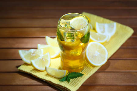 Iced tea with lemon and mint on wooden table photo