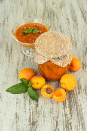 Apricot jam in glass jar and fresh apricots, on wooden background photo