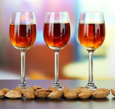 amaretto: Glasses of amaretto liquor and roasted almonds, on bright background