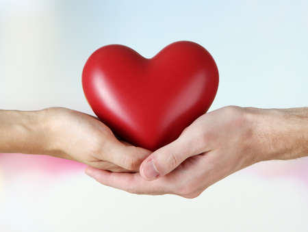 Heart in hands on light background photo