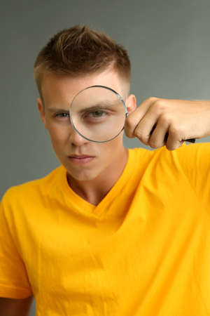 Young man looking through magnifying glass on grey background photo