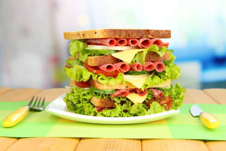 Huge sandwich on wooden table, on light background photo