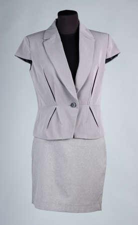 Chaqueta gris y una falda gris en maniqu�, sobre fondo gris photo