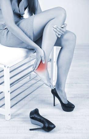 dolor muscular: Muchacha con el pie dolorido en tonos de gris