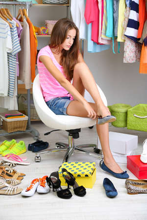 Beautiful girl chooses shoes in room  photo