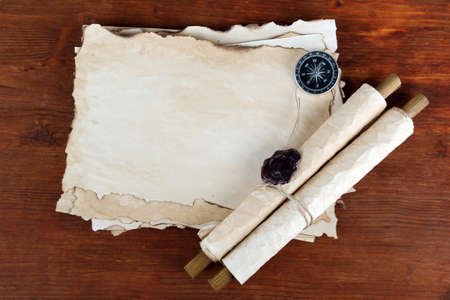 Old paper, scrolls and compass on wooden background photo