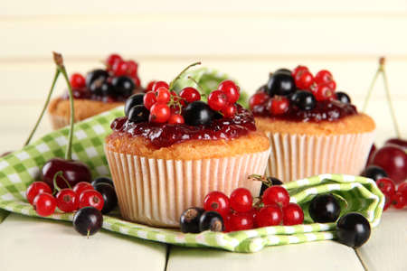 Tasty muffins with berries on white wooden table photo