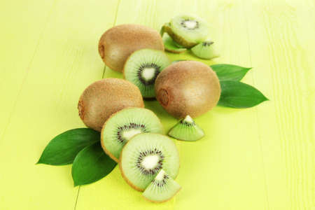 Ripe kiwi on green wooden table close-up photo