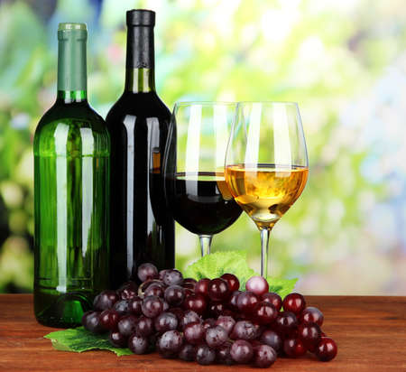 Wine bottles and glasses of wine on bright background photo