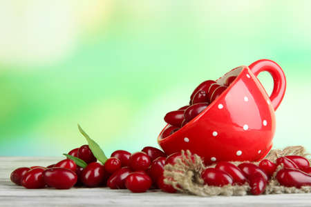Fresh cornel berries in red cup on wooden table photo