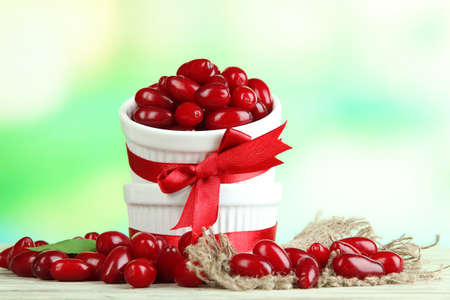 Fresh cornel berries in white cups on wooden table photo