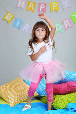 Little girl dancing on bed in room on grey wall background photo