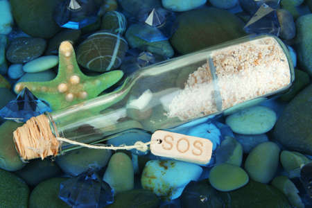 Bottle with letter on sea bottom with shells and stones photo