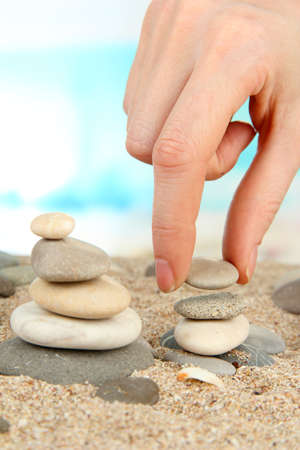 builds: Hand builds tower of sea stones on sand on bright background
