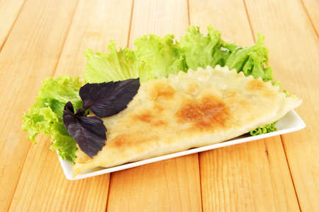Tasty cheburek with fresh herbs on plate,on wooden background photo
