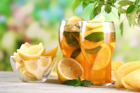 ice tea: Iced tea with lemon and mint on wooden table, outdoors