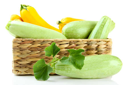 Raw yellow and green zucchini in wicker crate, isolated on white photo