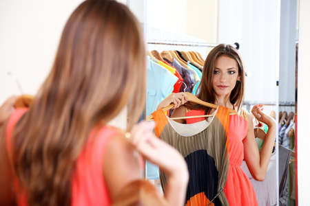 Beautiful girl trying dress near mirror on room background photo