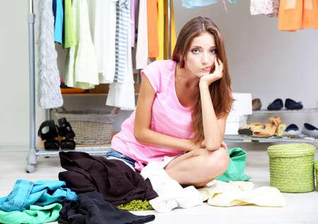 Mooi meisje denken wat te kleden in walk-in closet Stockfoto