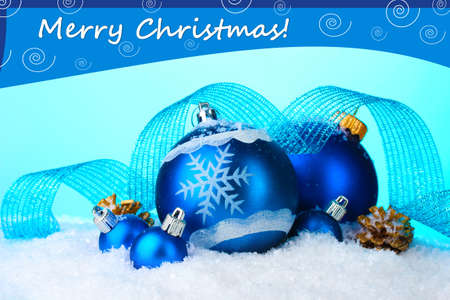 group of christmas baubles: Beautiful blue Christmas balls in snow on blue background