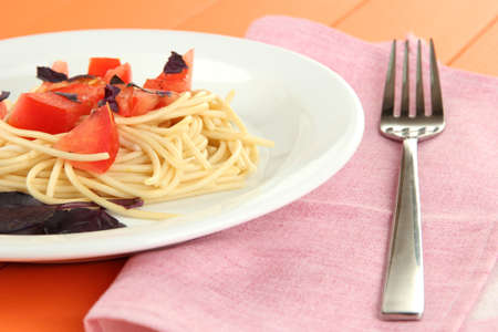 Spaghetti with tomatoes and basil leaves on napkin on wooden background photo