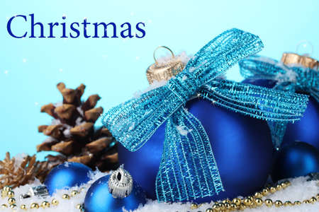 blue christmas background: Beautiful blue Christmas balls and cones on snow on blue background Stock Photo