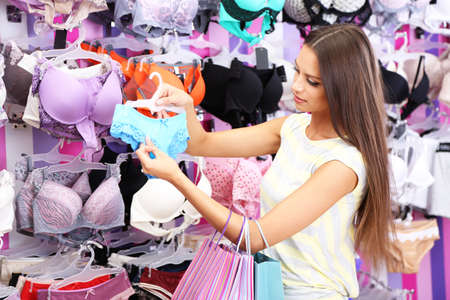 Beautiful young woman in shop with underwear Imagens