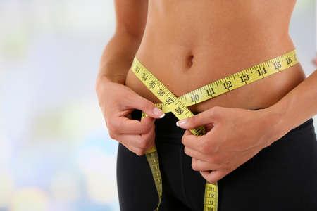 vientre femenino: Chica delgada con cent�metro aislados en blanco