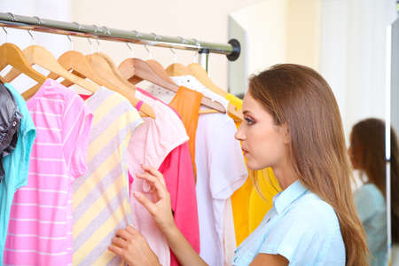 blouses: Beautiful girl chooses clothes on hangers on room background