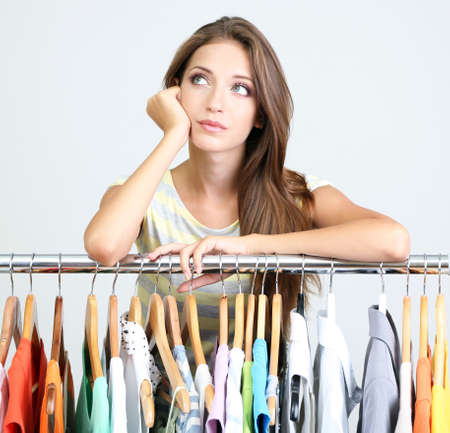 clothing: Beautiful young woman near rack with hangers