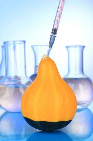 Injection into fresh pumpkin on blue background photo