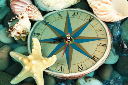 Clock on sea bottom with shells and stones photo