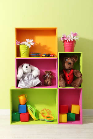 Bright shelves of different colors with toys on wall background photo